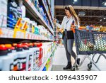woman can't decide what shampoo ... | Shutterstock . vector #1096435907