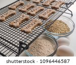 Small photo of Homemade dog treats with the word Woof on them cool on a rack, accompanied with ingredients eggs, oats, and whole wheat flour