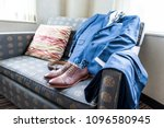Small photo of Closeup still life arrange on blue couch with Men's leather new brown shoes, socks, watch, suit for getting ready wedding preparation in room