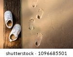 Small photo of Children Learn Beyond Classroom Concept, Kids Shoes Lay on the Wooden Timber, Sand Beach with Footprint as background, Top view