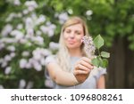 girl holding a sprig of lilac | Shutterstock . vector #1096808261