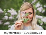 girl holding a sprig of lilac | Shutterstock . vector #1096808285