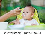 mother hand feeding food into... | Shutterstock . vector #1096825331