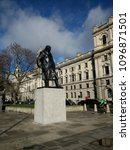 Small photo of Westminster London England - March 7 2018: view of the famous black statue of Prime Minister Sir Winston Churchill in Parliament Square near House of Parliament and Abbey on stone plinth from below