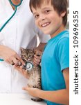 Veterinary care concept with young boy and his cat at the doctor - stock photo