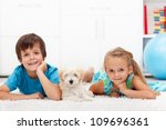 Happy kids with their pet - a fluffy dog - laying on the floor - stock photo