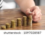 man stacking coins on table.... | Shutterstock . vector #1097028587