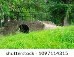 Small photo of green filed and brick sluice bridge in Klundert, The Netherlands