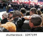 This is a shot of people looking on at a parade. - stock photo