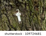 little metal cross on a mossy tree trunk in the forest - stock photo