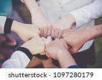 Small photo of Team fist bump together to form team spirit concept