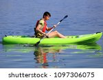 young teenage boy in a kayak on ... | Shutterstock . vector #1097306075