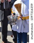 Small photo of an altar boy holding lit water and a sprinkler