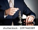 Small photo of business person wearing suit and aligning stones up, which represents patience and log term business plans.