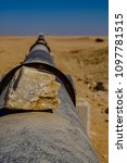 Small photo of Focus on piece of silica rock on iron pipe stretching to horizon in Namib Desert carrying water supply from desalination plant in Swakopmund to uranium mine