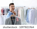 Young Man Holding Hanger With...