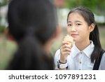 asian teenager eating icecream... | Shutterstock . vector #1097891231