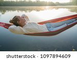 young woman by the lake hanging ... | Shutterstock . vector #1097894609