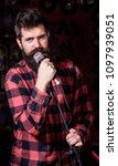Small photo of Man with calm face holds microphone, singing song, black background. Guy likes to sing rock songs. Musician with beard and mustache singing song in karaoke. Vocalist concept