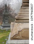 Detail of beautifully carved corner of large stone funeral monument in Mount-Royal Cemetery, with other monument in soft focus background, Montreal, Quebec, Canada