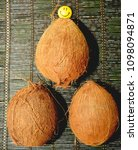 three coconuts on a black... | Shutterstock . vector #1098094871