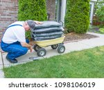 Small photo of Man in overalls crouching to fix a puncture on a wheelbarrow loaded with a stack of bags of mulch for the garden