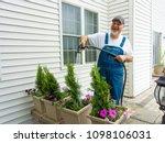 happy man enjoying watering his ... | Shutterstock . vector #1098106031
