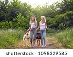Stock photo happy laughing young women walking their dogs along a grassy rural track in spring together sharing 1098329585