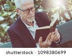 mature man reading a book...   Shutterstock . vector #1098380699