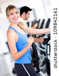 Happy woman training at the gym on cross trainer - stock photo