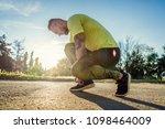 young handsome man tying shoe...   Shutterstock . vector #1098464009