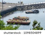 Small photo of GEOJE ISLAND, SOUTH KOREA - MAY 13, 2018 : Flat top pontoons with buoys and nets on the deck moor at the shore near Samsung Heavy Industries or SHI in Geoje island, South Korea.