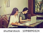 two young women sit at the desk.... | Shutterstock . vector #1098890324