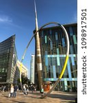 """Small photo of CARDIFF, WALES - MAY 2018: The """"Alliance"""" sculpture on The Hayes in Cardiff city centre. It comprises a stainless steel hoop and arrow."""