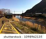 Small photo of Kamo, Shizuoka, Japan - February 10th, 2013: Children play along the river side at Kawazu in winter
