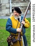 Small photo of Falmouth, Cornwall, UK - April 12 2018: Historical military re-enactor dressed in bleu and yellow Tudor clothes with leather equipment with a working musket
