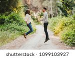 couple jumping and laughing in... | Shutterstock . vector #1099103927