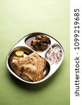 Small photo of Mini Mutton/gosht curry Thali with chapati/roti, popular indian lunch/dinner menu. served in a stainless steel oval plate with salad. selective focus