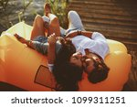 young couple lying in a lazy... | Shutterstock . vector #1099311251