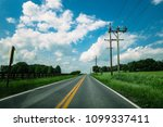 a winding country road on a... | Shutterstock . vector #1099337411