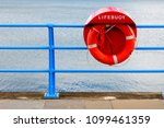 Small photo of Red lifering life preserver, live saver on a rope beside the sea.
