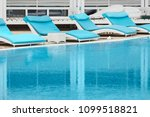 four turquoise loungers by the... | Shutterstock . vector #1099518821