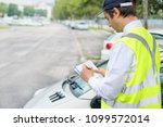 parking officer writing a... | Shutterstock . vector #1099572014