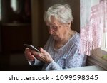 elderly woman with a smartphone ... | Shutterstock . vector #1099598345