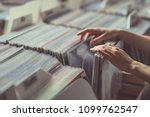 women's hands browsing records... | Shutterstock . vector #1099762547