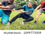team competing in tug of war | Shutterstock . vector #1099773509