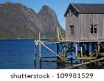 Old deteriorated fishing port by the fjord on Lofoten islands in Norway - stock photo