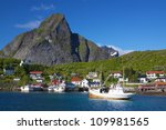 Picturesque town of Reine with fishing boats in the fjord on Lofoten islands in Norway - stock photo