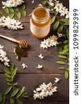 Small photo of Acacia honey and flowering acacia on wooden table
