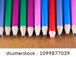 Small photo of black lead pencils lie in a row, one pencil has a red core and put forward , small depth of sharpness